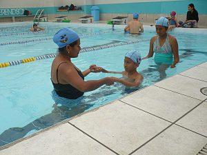 Arturo avec sa professeure de natation, et sa sœur Cielo.